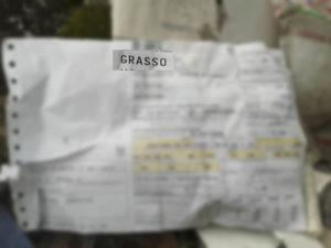 La polizza d'assicurazione fra i rifiuti in cui si legge il cognome dell'assicurato: Grasso (il resto è stato nascosto)