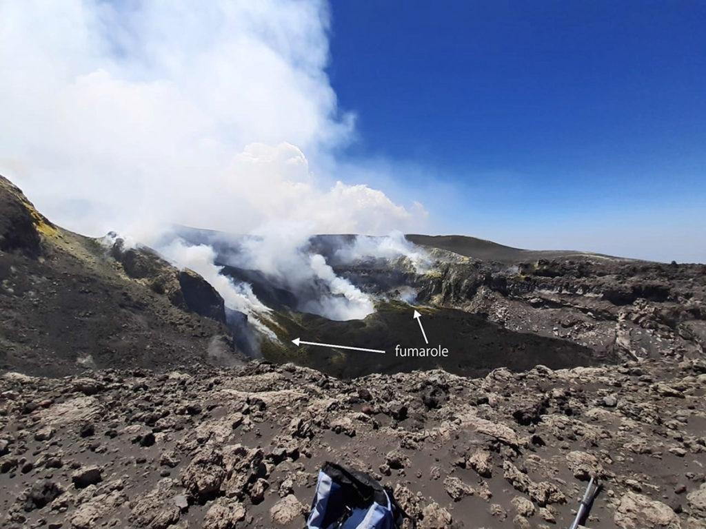 Panoramica del fondo di BN ripresa durante il sopralluogo del 3 luglio dal bordo occidentale dell'orlo craterico (foto E. De Beni). Al centro si osserva il cratere a pozzo formatosi al fondo del cratere. Sono visibili anche i sistemi di fumarole presenti sia lungo le colate provenienti da VOR (a sinistra) che nel settore meridionale del fondo craterico. Immagine tratta dal Bollettino Settimanale del 07/07/2020